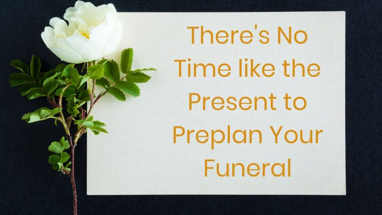 White gardenia with a sign with writing that says there is no time like the present to preplan your funeral