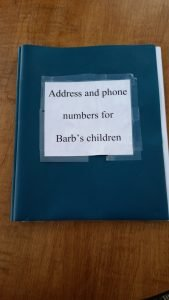 three hole plastic binder with name, address and phone numbers on each page